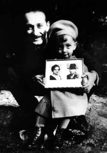 Artur Huppert of Czechoslovakia holds his child, Peterle, and displays the photo of his parents, Rosinka and Jusekl Huppert of Poland, 1941. This visual correspondence between Artur and his parents enables the child, parent, and grandparents to be in the same family portrait despite the challenge of geographical distances. It is probable that it was Rozinka and Jusekl who brought the photos to Auschwitz-Birkenau.