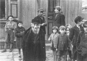 An elderly Jewish man stands among a group of children in a ghetto
